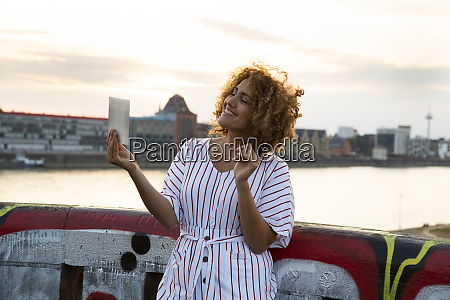 smiling woman with curly hair holding