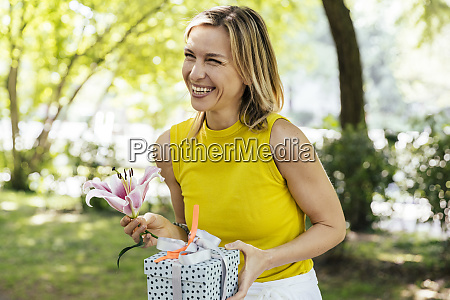happy woman in nature holding lily