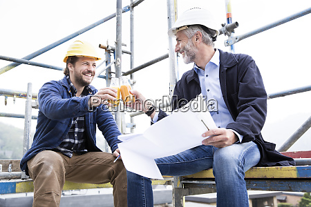 architect and construction worker toasting drinks