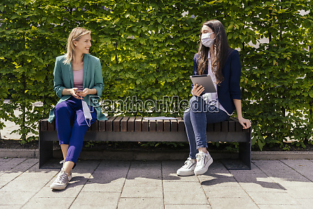 two businesswomen sitting on bench outside