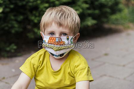 portrait of boy wearing a face