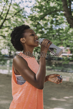 sportive young woman drinking water from