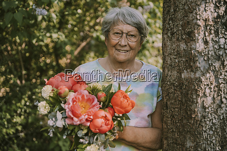 senior woman holding fresh peony bouquet