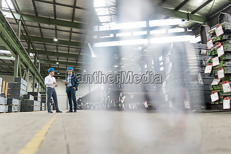 two businessmen talking in a factory