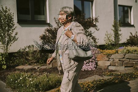 elderly woman walking outdoors on sunny
