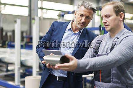 businessman and worker examining steel pipe