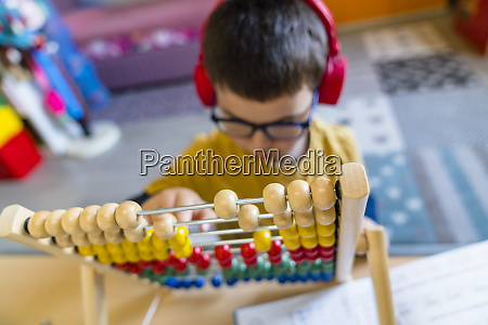 boy calculating with abacus while sitting