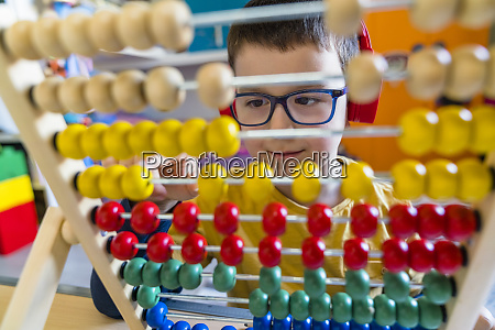 boy calculating with colorful abacus at