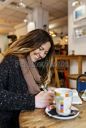 woman writing in notebook in coffee