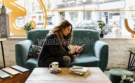 woman using smartphone sitting on couch