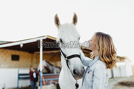 woman stroking a horse on a