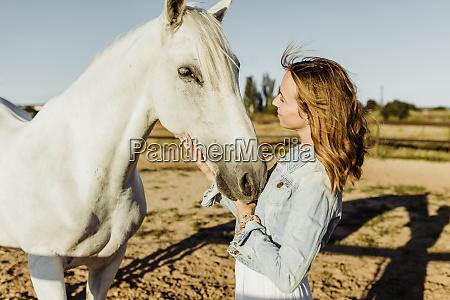 woman stroking grey horse