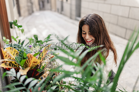 smiling woman placing plants outside shop