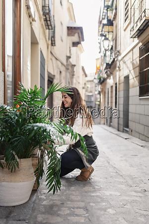 female florist placing plants outside flower