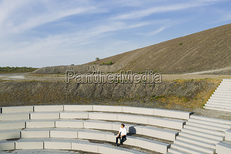 male professional sitting at amphitheater steps