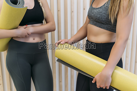 two sporty women holding gym mats