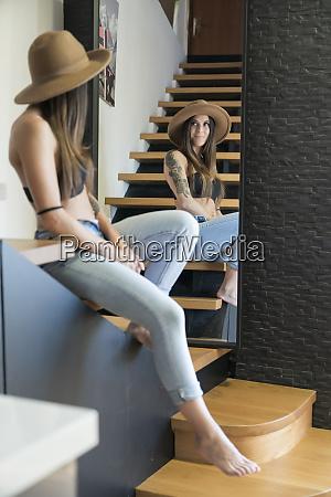 woman wearing hat looking in mirror