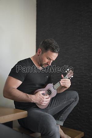 man playing ukulele while sitting on