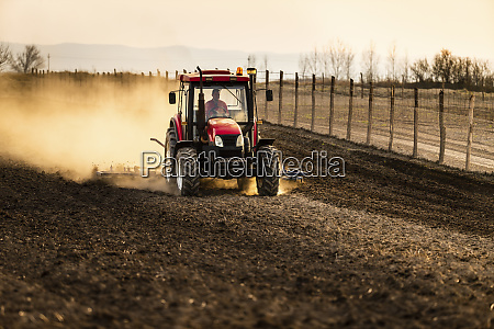 farmer in tractor plowing agricultural land