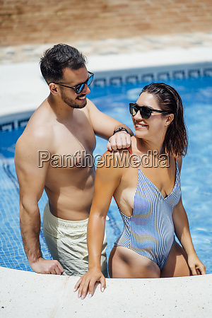 couple with sunglasses at pool edge