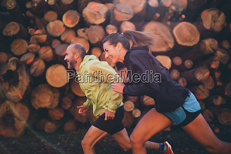 smiling couple running against logs in