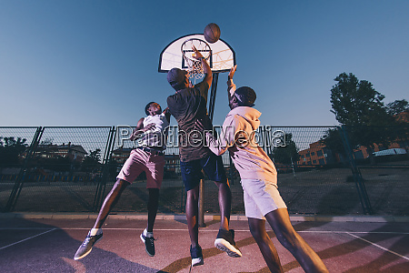 male friends playing basketball against clear