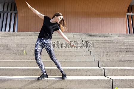 carefree woman with arms outstretched standing