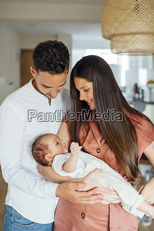 loving parents carrying baby boy at