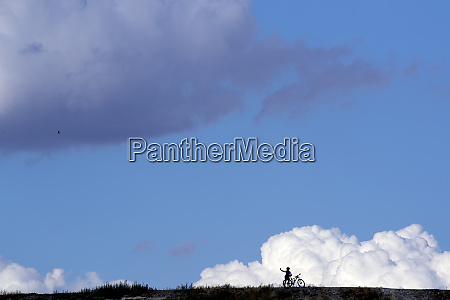 silhouette cyclist standing field against cloudy