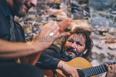 man playing flamenco on guitar while