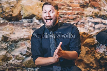 bearded singer clapping hands while singing