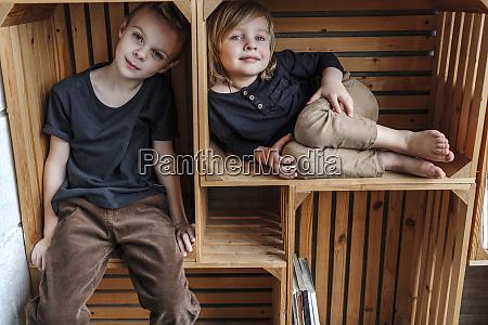 portrait of boys sitting in wooden