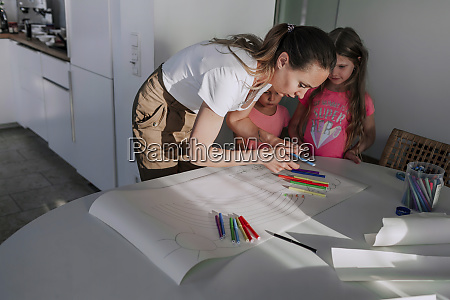 mother assisting daughters in drawing on
