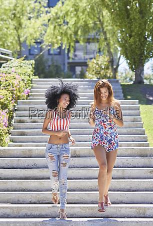 girlfriends walking in park