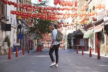 young man walking on street chinatown