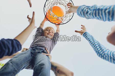 happy boy putting basketball in hoop