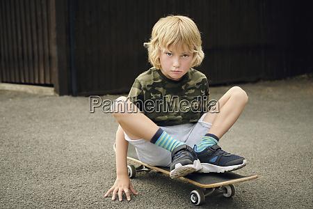 cute boy sitting on skateboard at