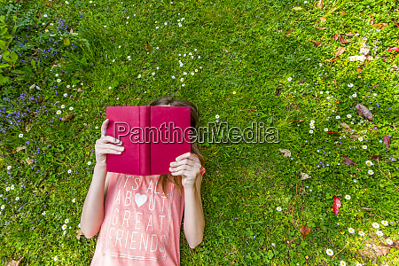 girl lying on meadow reading a