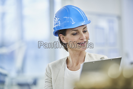 mature female manager in blue hardhat