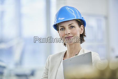 confident female manager wearing blue hardhat