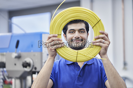 confident male worker looking through rolled
