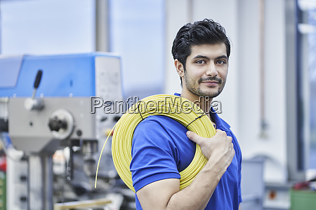 confident male worker carrying rolled up