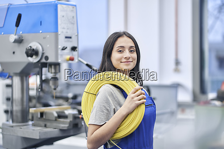 happy female worker carrying rolled up