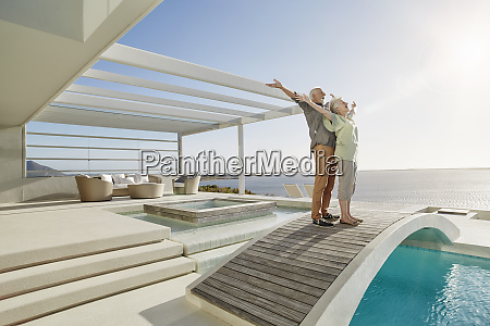 carefree senior couple standing on bridge