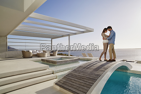affectionate couple standing on bridge above