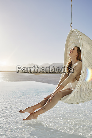 happy woman relaxing in hanging chair