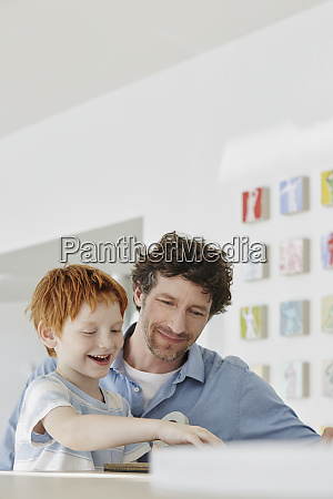 father playing with happy son in