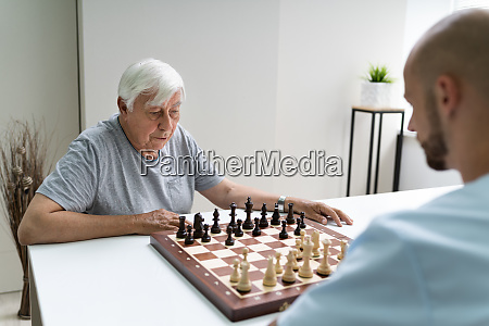elderly senior playing chess with caregiver