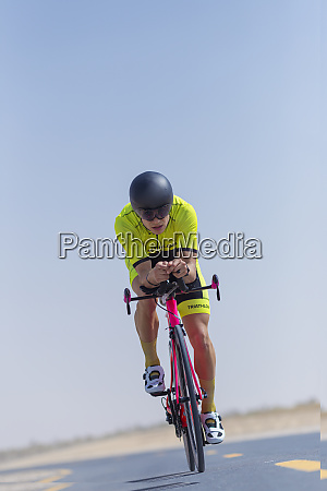 determined male cyclist riding bicycle on