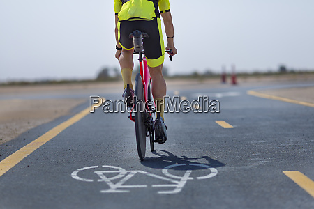 cyclist riding bicycle on road at